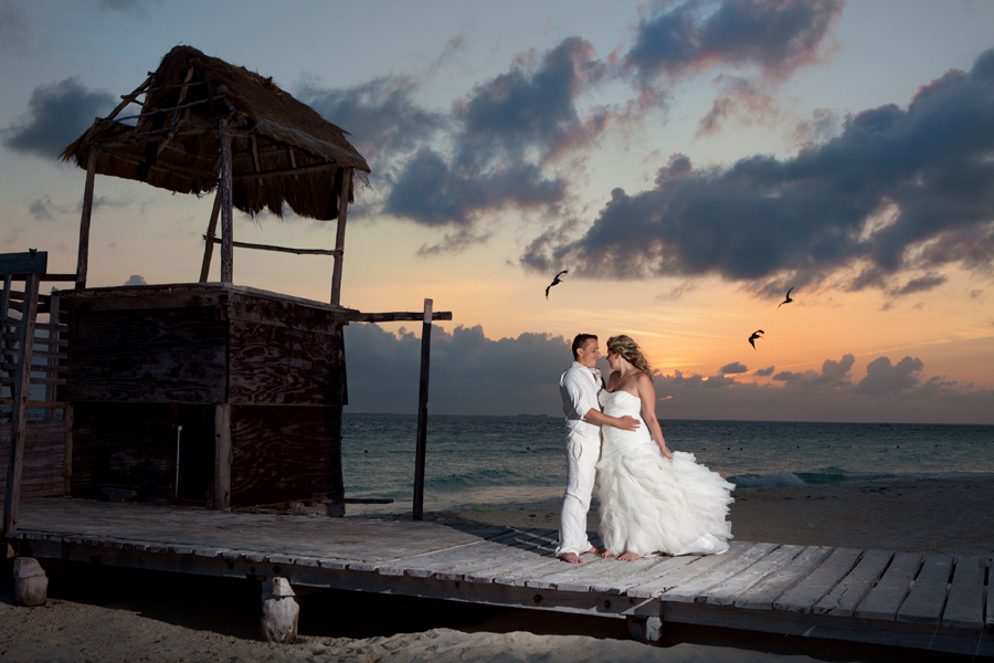 Bride and groom kissing at sunset on beach.