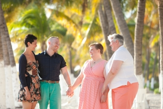 Same sex family holding hands on beach in Mexico